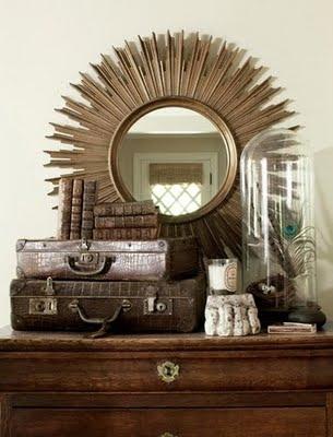 Bell jar, sunburst mirror, vintage suitcases