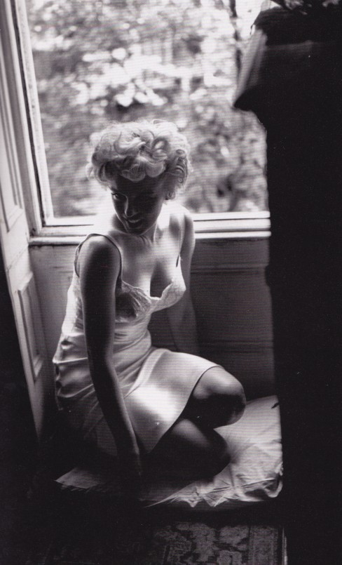 Marilyn Monroe in a slip, looking out window